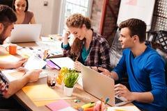 快乐的四个同事谈论新的项目 库存图片