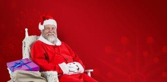 快乐的圣诞老人的综合图象坐与大袋的椅子圣诞节礼物 免版税库存照片