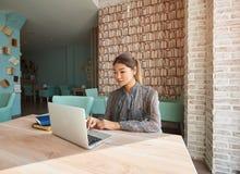快乐的在便携式计算机上的妇女观看的录影,当等待她的命令咖啡馆时 库存照片