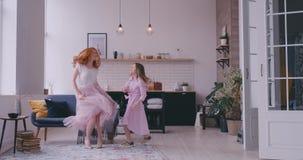 快乐的在客厅在家移动的跳舞的母亲小的女儿身分对一起喜爱的歌曲 孩子有 股票录像