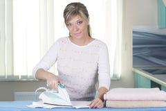 年轻快乐的在家庭内部的妇女电烙的衣裳 库存图片