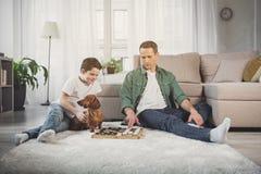 快乐的在家扮演验查员的父亲和男孩 免版税库存图片