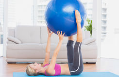 快乐的在腿之间的适合白肤金发的举行的锻炼球 库存照片