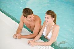 快乐的夫妇乐趣有池游泳年轻人 免版税库存照片