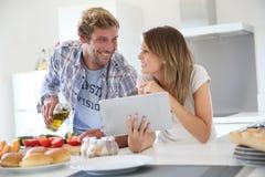 快乐的夫妇在准备汉堡包的厨房里 免版税图库摄影