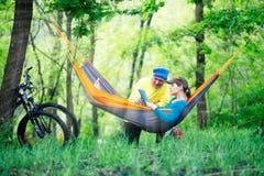快乐的夫妇在吊床放松并且使用片剂个人计算机 库存图片