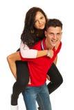 快乐的夫妇扛在肩上 免版税库存图片