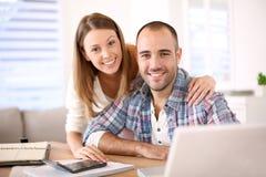 年轻快乐的夫妇计算的预算 免版税库存照片