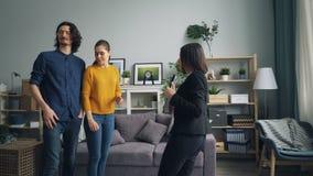 快乐的夫妇谈话与看新的公寓的不动产房地产经纪商户内 股票视频