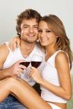 快乐的夫妇饮用的酒年轻人 免版税库存图片