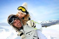 快乐的夫妇画象在多雪的山的 免版税库存图片