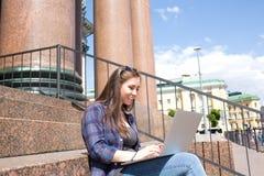 快乐的女学生为路线工作做准备使用现代便携式计算机 免版税库存照片