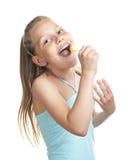 快乐的女孩一点棒棒糖唱歌 免版税库存照片