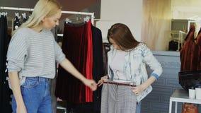 快乐的女孩一起选择长裤,当shanding在衣裳精品店时 他们采取时髦的裤子 影视素材