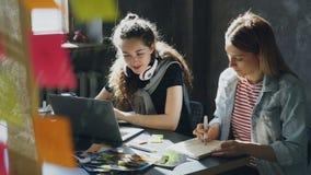 快乐的女孩与膝上型计算机一起使用并且听到音乐,然后离开耳机和谈话与她的工友 股票视频
