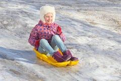 快乐的女孩从一座冰冷的山乘坐在塑料雪撬 在寒假期间,孩子走 免版税库存图片
