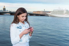 年轻快乐的女孩叫与手机,当享受g时 免版税库存图片