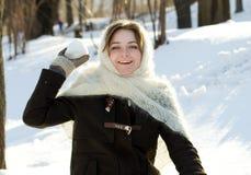 快乐的女孩在一个被编织的围巾冬天投掷雪俄国人冬天 免版税库存图片