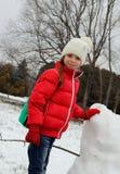 快乐的女孩在强光雪人附近站立 免版税库存图片