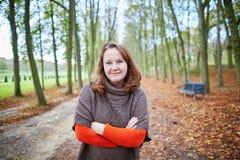 快乐的女孩在森林或公园里在一秋天天 免版税库存图片