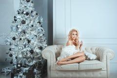 快乐的女孩坐在家庭舒适的一个沙发 免版税图库摄影