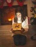 快乐的女孩坐地板在壁炉和打开的Christma 库存图片