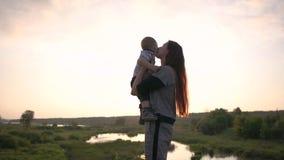 快乐的女孩投掷并且亲吻她的儿子,站立在慢动作的草甸 影视素材