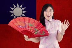 快乐的女孩拿着与台湾旗子的一个爱好者 免版税库存图片