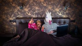 快乐的女孩显示赞许姿态和说谎在与滑稽的男朋友的床上 库存图片