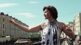 快乐的女孩波浪在河堤防的城市老镇递移动的手指 股票录像