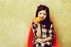 快乐的女孩用在手中微笑在塑料椅子的桔子 图库摄影