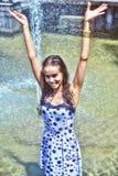 快乐的女孩用在摆在喷泉的背景的一根湿礼服和棕色头发的被举的手 免版税库存图片
