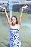 快乐的女孩用在摆在喷泉的背景的一根湿礼服和棕色头发的被举的手 图库摄影