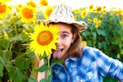 快乐的女孩用在显示舌头的柳条帽子的向日葵 免版税图库摄影