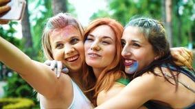快乐的女孩绘了与五颜六色的粉末笑并且在侯丽节费斯特以后做selfies 股票录像
