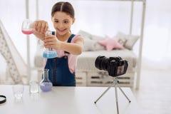 快乐的女孩陈列颜色怎么在化工烧瓶改变 免版税库存图片