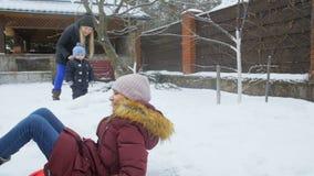 快乐的女孩骑马慢动作录影在雪撬的在房子后院 股票视频