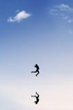 快乐的女实业家在清楚的天空飞跃 免版税库存照片