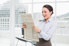 快乐的女实业家读书报纸在办公室 库存照片