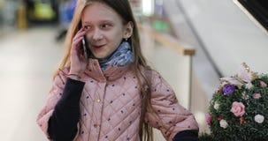 快乐的女小学生谈话在一个手机在一个购物中心 股票视频
