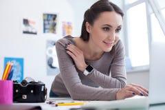 快乐的女性摄影师与计算机一起使用 图库摄影