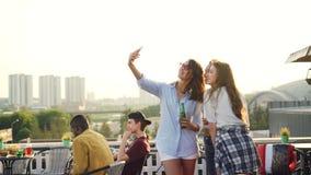 快乐的女性朋友采取与智能手机的selfie和笑的站立在与饮料的屋顶在瓶 股票视频