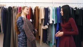 快乐的女推销员服务客户,穿礼服的帮助在精品店的衣橱附近 影视素材