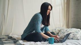 快乐的女生在家学习与计算机一起使用坐看屏幕的床,键入和微笑 股票录像