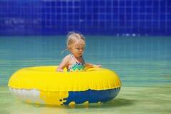 快乐的女婴游泳滑稽的画象在水公园 免版税库存图片
