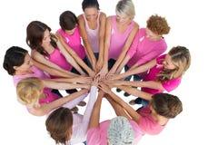 快乐的妇女加入了乳腺癌的圈子佩带的桃红色 免版税库存图片