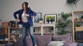 快乐的妇女唱歌的和跳舞的在家听到在耳机的音乐 股票录像