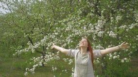 快乐的妇女在一个开花的庭院、情感和幸福里享受夏天 股票视频