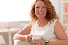 快乐的妇女在长沙发辞职 免版税库存照片
