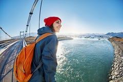 快乐的妇女在brige走在Jokulsarlon冰盐水湖 免版税库存图片
